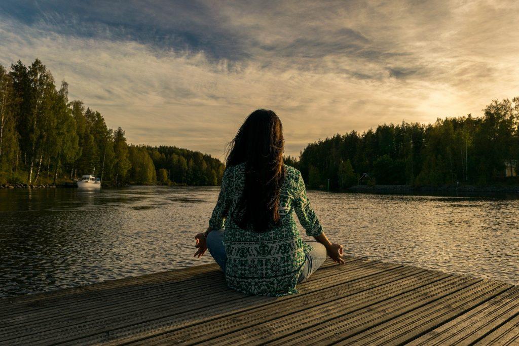 Women, meditating near a river